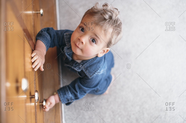Baby boy plays with knob of drawers
