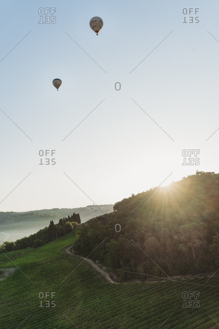 August 2 2019: Hot air balloons flying over champagne Vineyards at sunset in Tuscany