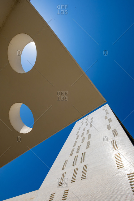 Facade of a modern building and a wall with circular holes in an area of ??modern architecture