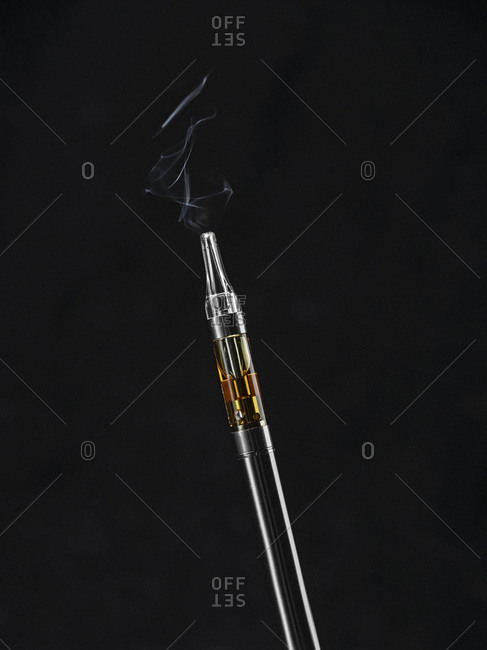 Full marijuana oil cartridge in a vaporizer pen on a black background with smoke.