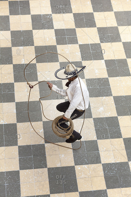 A young man dressed as a charro jumps the rope on the floor of a patio in Lagos de Moreno, Jalisco.