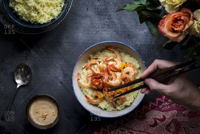 Hand holding chopsticks to eat basmati Indonesian shrimp rice