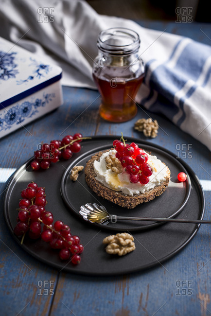 Fresh currant and ricotta toast with walnut honey dressing on a blue wooden background