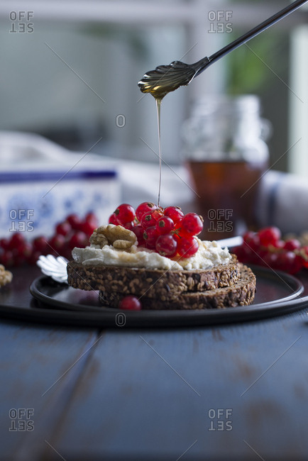 Honey being drizzled on fresh currant and ricotta toast with walnuts