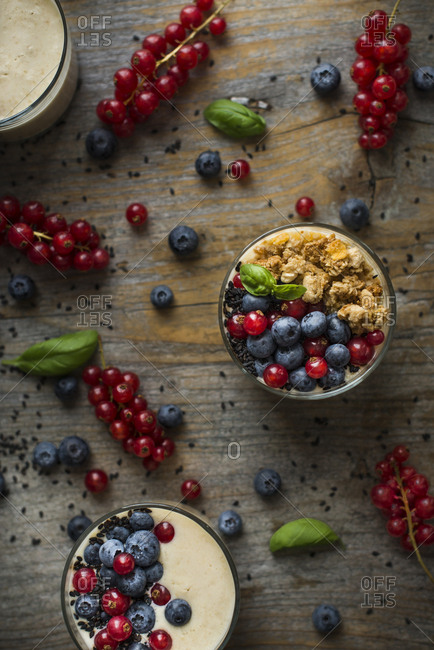 Overhead view of smoothie glasses with muesli, fresh currant and blueberry mixed with basil and sesame