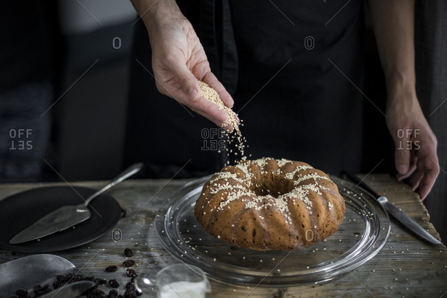 Hand decorating a sorgho cake with white sesame seeds