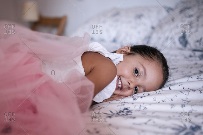 Caucasian girl with pink tutu lying on a bed