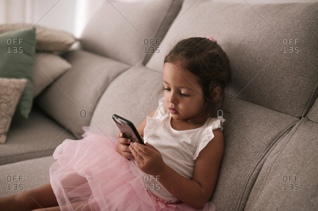 Caucasian girl with tutu sitting on a sofa looking at a mobile phone screen