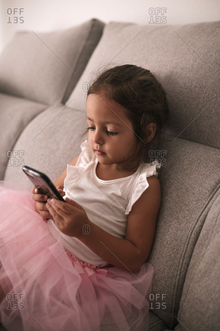 Little girl with tutu sitting on a sofa looking at a mobile phone screen
