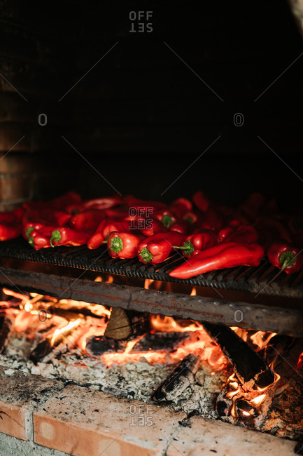 Red peppers cooking in a wood fire oven