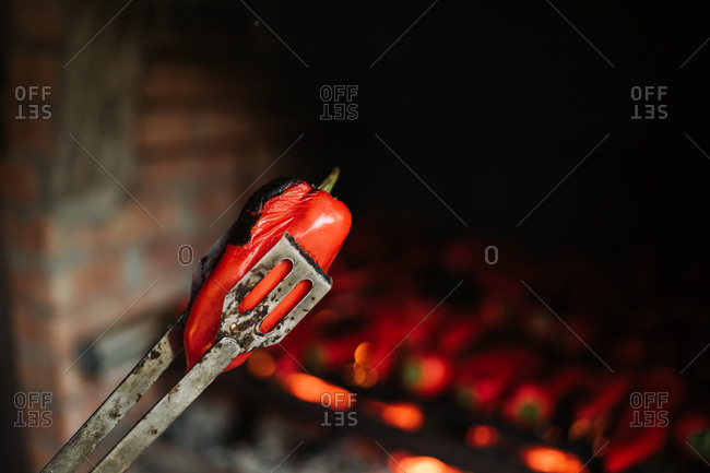 Tongs holding a red pepper cooked in a brick oven