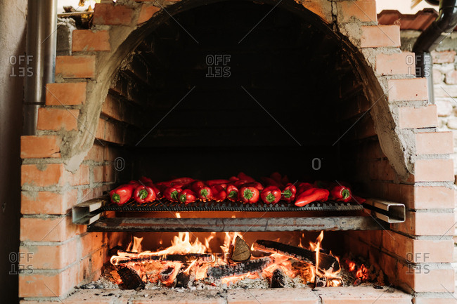 Red peppers cooking in a brick oven