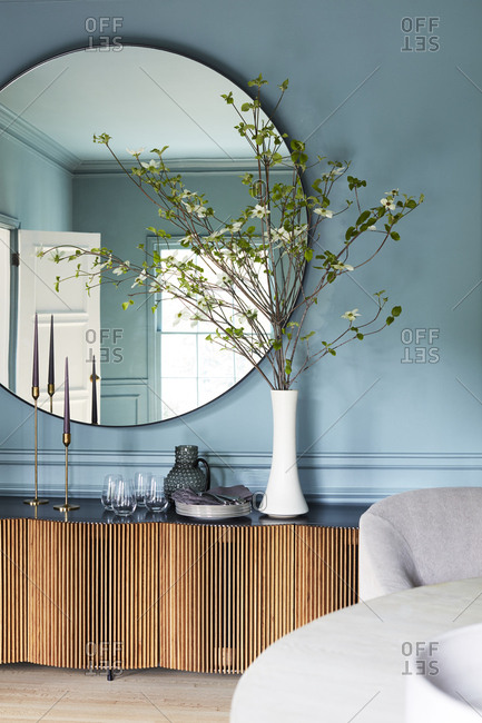 Interior of Los Angeles home with blue walls and a large round mirror above a table