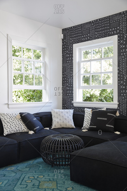 Los Angeles, California - May 17, 2019: Living room with dark sectional sofa and pattern wallpaper