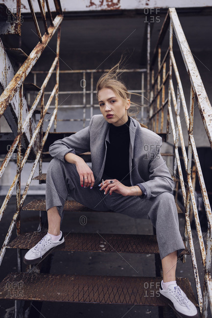 woman sits on steel steps in a business suit
