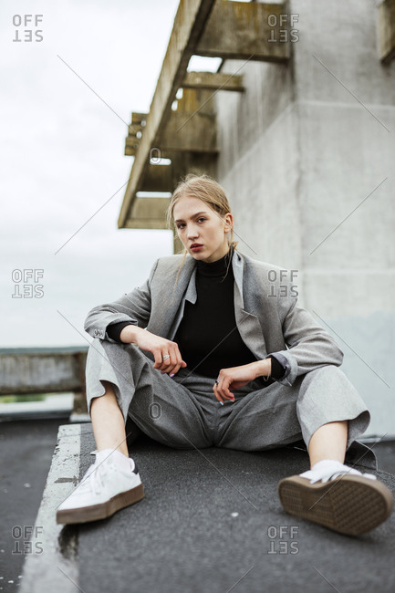woman sitting on the roof of a house in a business suit