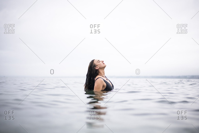 Young Woman Enjoying the Ocean on a Rainy Day