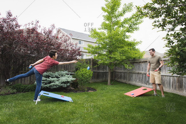 Father and son playing corn hole game in the backyard together.