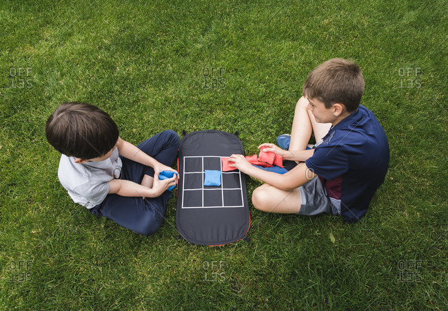 High angle shot of two boys playing tic tac toe game on the grass.