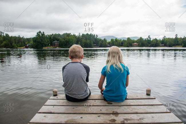 Girl and boy sitting at the edge of dock of lake