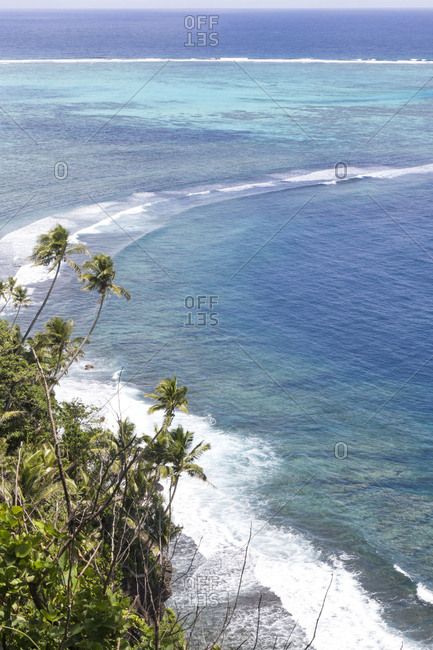 Aerial view of waves breaking on reef and tropical palm trees, Samoa