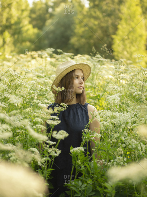 Young woman in hat standing in field against trees and looking away