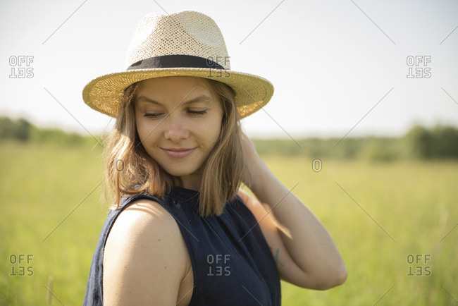 Content woman in hat standing in field against sky enjoying sunny day