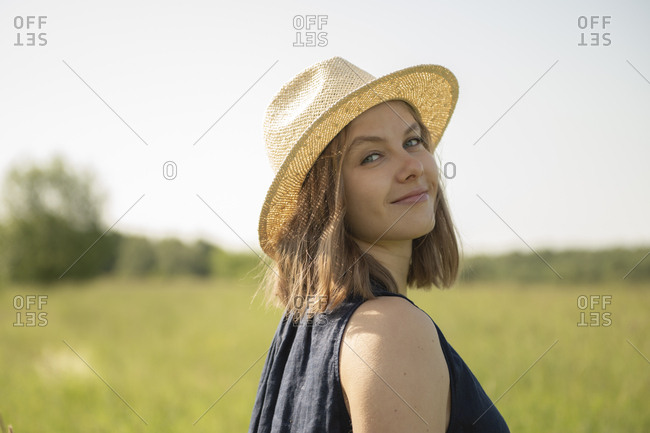 Smiling young woman in hat standing in field and looking at camera