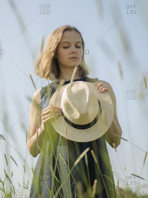 Woman with hat in hands standing in a field amidst grass by sunny day