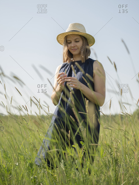 Low angle view of woman standing in a field amidst grass by sunny day