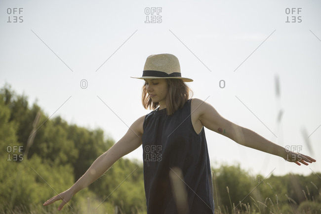 Woman walking in a field with her arms like a plane against blue sky