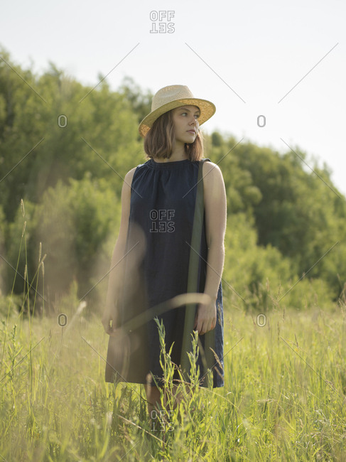 Young woman standing in a field amidst grass against sky by sunny day