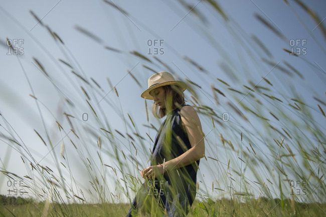 Young woman in hat enjoying nature and sunlight while walking in field