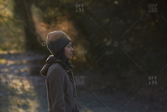 Side profile of Asian woman enjoying the cold weather blowing mist