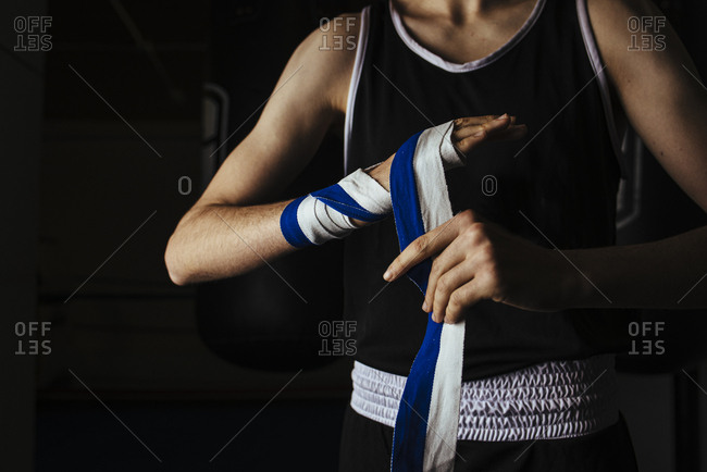 Young boxer placing hand bandages in gym before training.