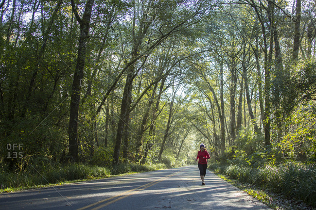 Adult woman running on road with a canopy of trees in Washington State