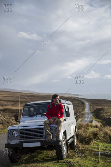 Adult man sitting on the hood of an SUV looking at ocean in Scotland