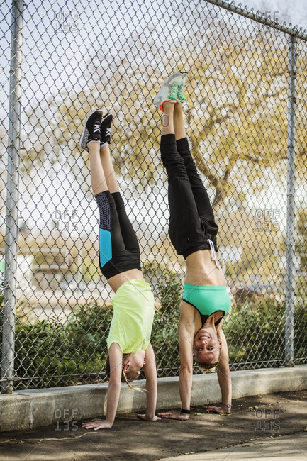 Mother and daughter doing hand stands outside against fence