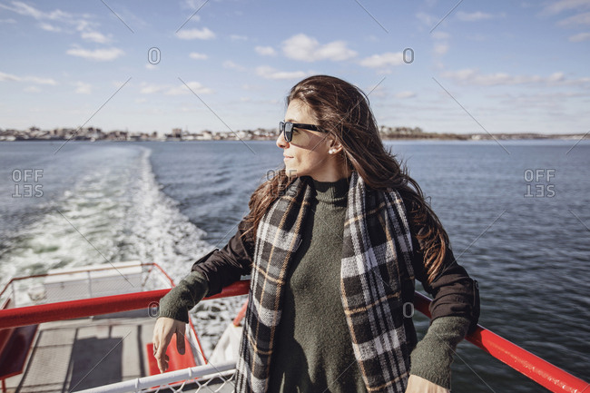 A woman leans against the railing of a ferry on a sunny day in Maine