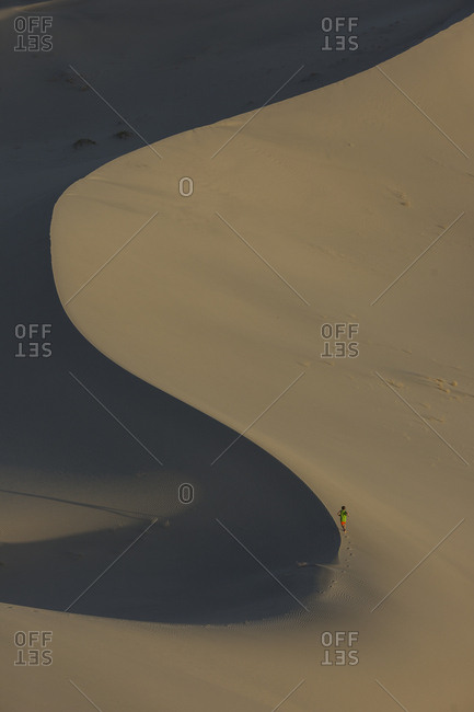 Boy, age 9 running along the spine of a sand dune in the desert