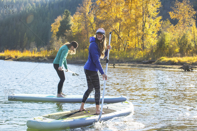 Two women laughing while stand up paddling on a river in Idaho.