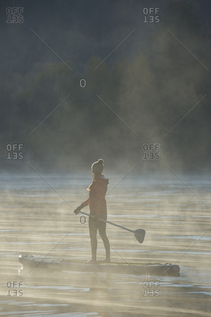 Misty morning stand up paddler on Lake Pend Oreille, Idaho.