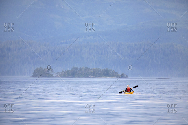 A solo male kayaker in middle of channel, Telegraph Cove, British Columbia, Canada