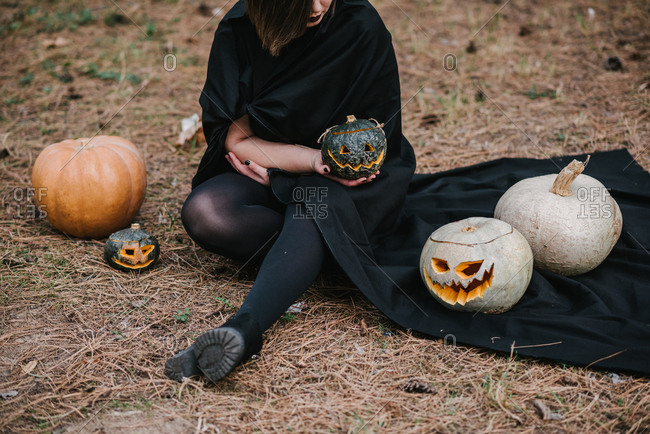 Vampire woman sitting with her pumpkins in pine field