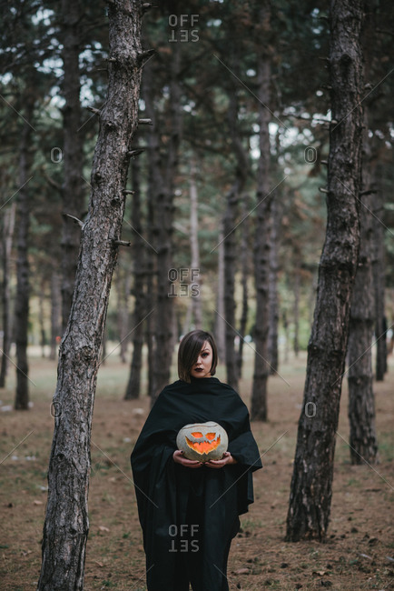 Lonely woman in forest holding pumpkin for halloween
