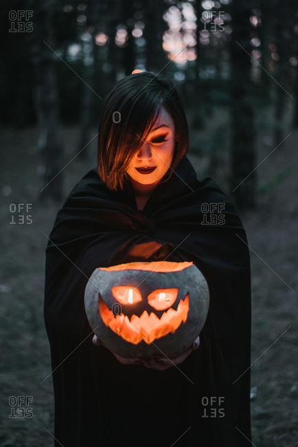 Woman in vampire costume holding scary carved pumpkin for halloween