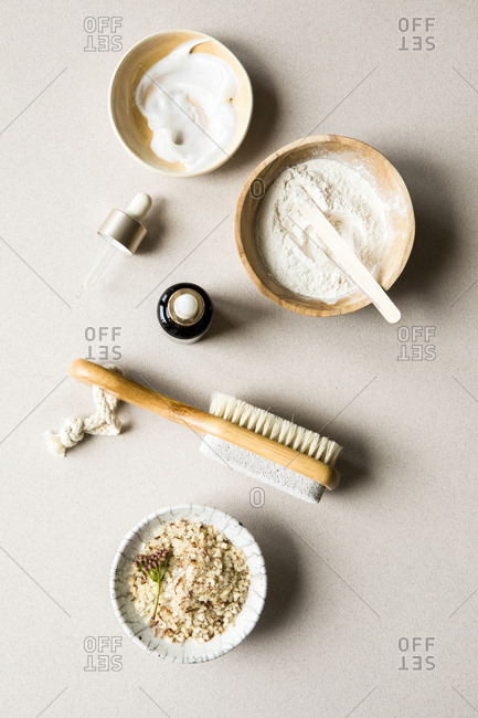Overhead view of 3 bowls containing cream, powder, and salt for beauty products