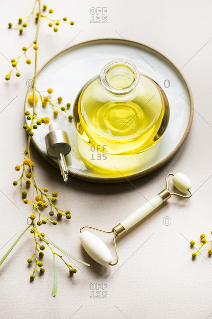 Bottle of oil on ceramic plate surrounded by yellow flowers and facial roller