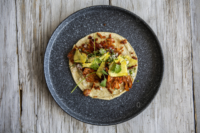 Overhead view of al pastor taco with pineapple, coriander and onion