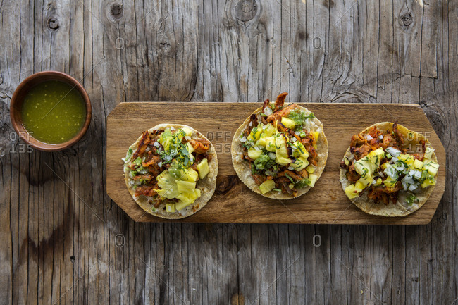 Overhead view of al pastor taco with pineapple, coriander, onion and chile sauce over a wooden background